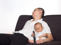 睡觉的爸爸,当照顾婴孩时 免版税库存照片