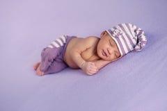 睡觉盖帽和裤子的微笑的女婴 免版税库存照片