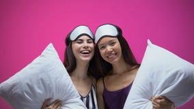 睡觉穿戴的微笑的妇女和拥抱的眼罩拿着枕头和,党 股票录像