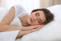 睡觉美丽的少妇,当在她的床上和舒适地时放松 为工作醒或是容易的 免版税库存照片
