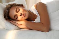 睡觉美丽的少妇,当舒适地和有福地时在床上 在她的面孔的光束黎明 免版税库存照片
