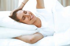 睡觉美丽的年轻和愉快的妇女,当舒适地在床上和有福地微笑时 库存图片