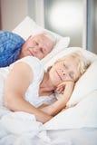 睡觉除在床上的丈夫以外的微笑的资深妇女 免版税库存照片
