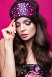 睡觉面具的滑稽的在桃红色背景的少妇和睡衣 秀丽表面 免版税库存照片