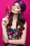 睡觉面具的滑稽的少妇和睡衣,在桃红色背景的甜点 秀丽表面 库存照片