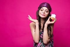 睡觉面具的滑稽的少妇和睡衣,在桃红色背景的甜点 秀丽表面 免版税库存照片