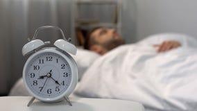 睡过头在早晨,警报的男性敲响在床头柜,时间安排上 免版税库存图片