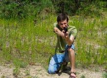 瞄准与一杆气动力学的枪的一个年轻人的画象 免版税图库摄影