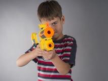 瞄准与玩具枪的男孩 免版税库存图片