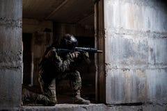 瞄准在废墟的战士一杆步枪 免版税库存图片