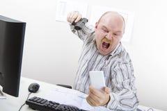 瞄准在手机的恼怒的商人枪书桌 免版税库存照片