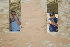瞄准手枪的两个人射击距离 免版税库存照片