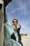 瞄准枪的女性警察通过残破的挡风玻璃 免版税库存图片