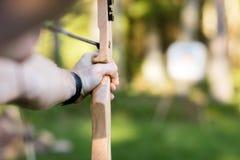 瞄准箭头的年轻运动员目标板在森林里 库存图片