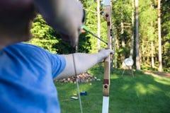 瞄准箭头的成熟运动员目标板在森林里 库存照片