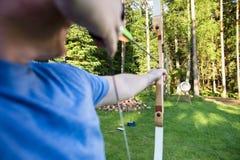 瞄准箭头的男性运动员目标板在森林里 库存图片