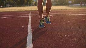 瞄准紧密人跳过在轨道的跨越横线的` s腿英尺长度体育场户外 佩带的蓝色运动鞋 股票视频