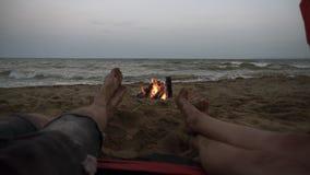 瞄准紧密青年人脚英尺长度从红色帐篷的在海滩 男性和女性腿有海视图和 股票录像