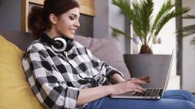 瞄准膝上型计算机开头的英尺长度由有耳机的一个微笑的女孩 女孩开始关于的通信 股票视频