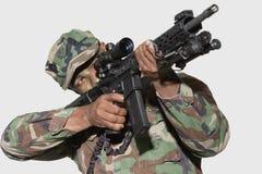 瞄准M4攻击步枪的美国陆战队战士反对灰色背景 免版税库存图片