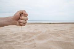 瞬间-沙子奔跑通过握紧的手指 库存图片
