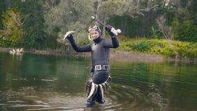 矛渔夫显示淡水鱼在水中在寻找以后在森林河 免版税图库摄影
