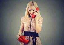 知道在电话的恼怒的白肤金发的妇女坏消息 库存照片