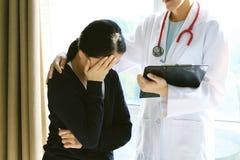 知道坏消息的患者,她是绝望和哭泣,医生支持和安慰她的患者 库存照片