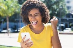 知道好消息的年轻拉丁妇女由电话 库存图片