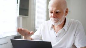 知道非常在他的便携式计算机上的英俊的年长老人坏消息筛选并且弄翻了 影视素材