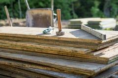 短槌、保护的手套和建造者平实在堆木 库存照片
