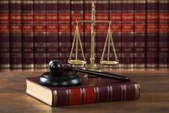 短槌和法律书与正义标度在表上 图库摄影