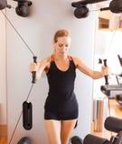 短的体育短裤的年轻美女和参与在健身房的健身一件黑无袖的球衣 库存图片