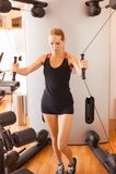 短的体育短裤的年轻美女和参与在健身房的健身一件黑无袖的球衣 免版税库存图片