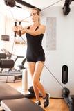短的体育短裤的年轻美女和参与在健身房的健身一件黑无袖的球衣 图库摄影