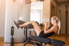 短的体育短裤的年轻美女在健身房的健身震动在体育教练员的腹肌 图库摄影