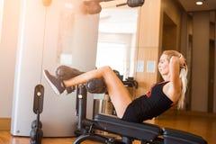 短的体育短裤的年轻美女在健身房的健身震动在体育教练员的腹肌 免版税库存图片