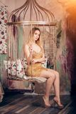 短的典雅的金黄礼服的年轻豪华时髦的白肤金发的妇女 免版税库存照片