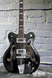 短的在白色砖背景的标度Gretsch低音吉他 免版税图库摄影