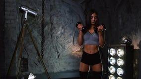 短的外套的性感的运动的女孩有户内哑铃的在石灰色墙壁的背景举她的手与 股票视频
