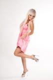 短的桃红色的跳舞的白肤金发的女孩礼服和高跟鞋在白色隔绝的她性感的腿,后侧方 免版税库存照片