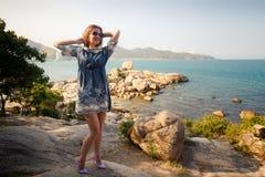 短的灰色连衣裙的女孩在岩石站立在海旁边反对城市 图库摄影