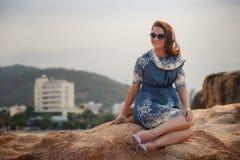 短的灰色连衣裙的女孩坐岩石展示腿反对城市 免版税库存照片