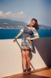 短的灰色连衣裙的深色的女孩由墙壁微笑反对海 免版税图库摄影