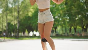 短的牛仔布短裤和白色T恤杉的女孩获得在晴天骑马的乐趣在GyroScooter的慢动作 影视素材
