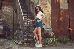 短的牛仔布短裤的,白色T恤杉和太阳镜亭亭玉立的女孩,摆在与城市自行车在一块老被放弃的砖附近 库存照片