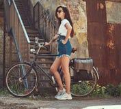 短的牛仔布短裤的,白色T恤杉和太阳镜亭亭玉立的女孩,摆在与城市自行车在一块老被放弃的砖附近 免版税库存图片