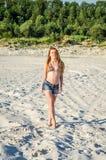 短的牛仔布短裤的有长的头发的比基尼泳装泳装走沿沙子的年轻迷人的女孩和挖掘沙子可提取industr 免版税库存照片