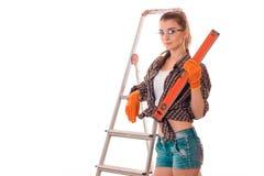 短的短裤和衬衣的可爱的女孩在一架小梯子附近在他的手上站立并且拿着测量的一个设备 免版税图库摄影