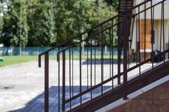 短的石楼梯户外特写镜头细节与金属防护简单的原始金属篱芭和扶手栏杆的由brigh点燃了 免版税库存图片